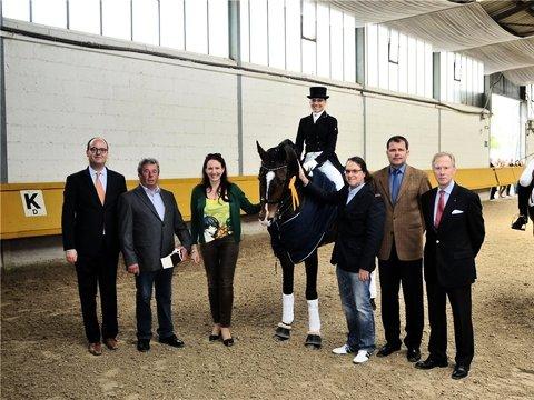 Siegerin mit Pferd und Gratulanten: Aileen Day auf Destino D (Mitte) entschied das Intermediare I für sich. Foto: Kehr